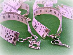Tape Measure Bracelet. Materials used: 2 folding ribbon clamps,1 lobster clasp, 2 jump loops, flexible tape measure, 1 scissor charm or sewing machine charm (optional). Very cute!