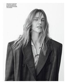 Photographed in black and white, Sasha Pivovarova wears Balenciaga plaid coat and button-up shirt