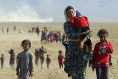 Displaced people from the minority Yazidi sect, fleeing violence from forces loyal to the Islamic State in Sinjar town, Iraq walk towards the Syrian border, on the outskirts of Sinjar mountain, near the Syrian border town of Elierbeh of Al-Hasakah Governorate August 11, 2014. REUTERS/Rodi Said
