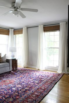 Large colorful, Persian rug paired with white curtains and bamboo shades styled by Claire Brody