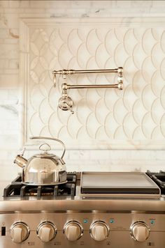 A modified fish scale backsplash behind the range is a lovely accent to the pot filler faucet and marble surround