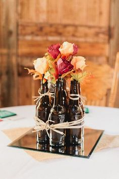 beer bottles used as centerpieces / http://www.deerpearlflowers.com/wine-bottle-vineyard-wedding-decor-ideas/