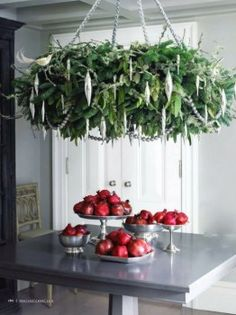 Hang a giant wreath over the dining table like a chandelier. Add some sparkling ornaments for a glam touch. Wouldn't this be perfect for Christmas dinner? — from Creative Christmas Wreath Ideas - Unique Ideas for Decorating with Wreaths Indoors, Winter Holiday Decorations.