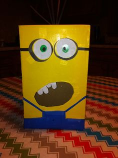 V-Day box DIY: Minions Valentine's day card box for school. Items you need: a shoe box, scissors, yellow wrapping paper, blue rapping paper, clear tape, one double sided black poster board, one piece white paper, green marker, black marker and spray glue. This is so simple my 5 yr old son helped for his PreK V-Day box project.  Paintedveilphotography@hotmail.com Jennifer Clark