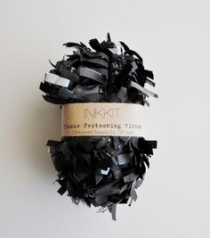 Packaging for 'Inkkit' black tissue festooning ribbon by Cait Lucas