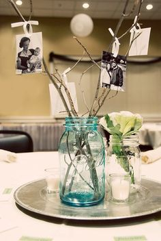 Easy DIY centerpiece - I like the idea of the branches and photos.  Could stick a couple in the flowers maybe for height?  Also, could use silver chargers to define your centerpiece if your driftwood was short. This would be so cute for a wedding by putting the bride and grooms baby pics on this! Could also use this as a way to number a table combine center piece with table number