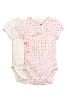 Lot de 2 bodies: CONSCIOUS. Bodies croisés à manches courtes en jersey souple de coton bio mélangé. Boutons-pression sur le côté et à l'entrejambe.