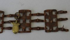 """Antique 18C Spiked Dog Collar With Coat Of Arms  Antique spiked dog collar measures 18"""" in length and is 4"""" in width. Condition is good. Has a brass coat of arms attached, could be a dog of royalty.  Item #5057 SOLD"""