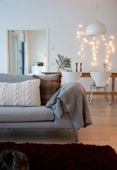crisp-white-living-room-with-tartan-and-knitted-scatter-cushions-and-fairy-lights