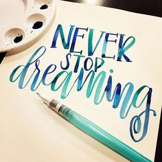 white sheet of paper, with the words never stop dreaming, written in blue waterc. - M collage - Ideen Watercolor Brush Pen, Watercolor Lettering, Watercolor Water, Calligraphy Letters, Modern Calligraphy, Caligraphy, Penmanship, Calligraphy Handwriting, Water Color Calligraphy