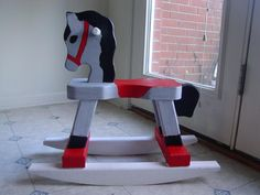 By a plain wooden horse at a craft store and decorate it with acrylic paint.  It makes for a great Christmas present/decoration.