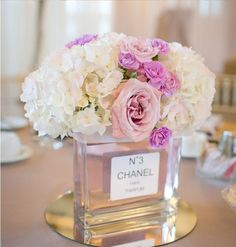 old perfume bottle as a flower vase...this is a cute centerpiece idea for a bridal shower - for a bride who loves Chanel.