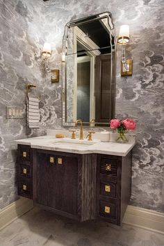 Elegant powder room showcases a gorgeous arch vanity mirror flanked by E.