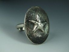 Sterling silver repousse ring with a starfish design.www.nrwoart.com