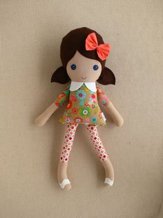 This is a handmade cloth doll measuring 20 inches. She is wearing a colorful tan, pink, and blue bird/flower print dress with coral polka dotted