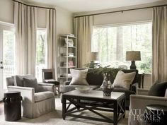 Neutral drapes hung toward ceiling keep this room open and light.