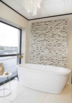 A beautiful white free-standing #bath contrasts against a neutral floor-to-ceiling #mosaic feature #wall