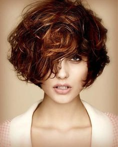 short curly dark brown hairstyle with auburn highlights