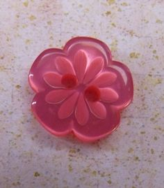Honeysuckle pink plastic button.