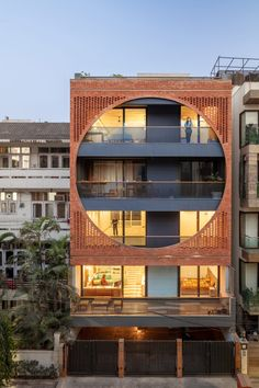 On the elevation facing the street, a perforated screen made from brick tiles extends across the full height of the upper three storeys. The square screen inscribes a large circle that frames the full-width balconies.