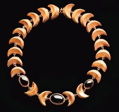 A ROMAN GOLD AND GARNET NECKLACE Circa 2nd-3rd Century A.D. Composed of twenty-two hollow crescent-shaped links, each with a plaster fill, joined by small loops, with three oval links in the center, each set with a cabochon oval garnet 14¼ in. (36.2 cm) long