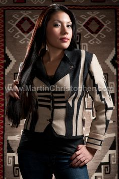 Our model is wearing a fitted Bolero created by Joyce Herrington from a Cheyenne Eagle blanket of the American Indian College Fund. It was designed by former U.S. Senator Ben Nighthorse Campbell of Colorado. The background of this fashion photograph is a 6' x 10' Bisti Navajo rug, circa 1950. The rug is made from natural handspun and analyne dyed wool. Available at Native Jackets on the Santa Fe Plaza in Santa Fe, New Mexico.