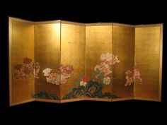 """Boldly painted six-panel folding screen (byobu) depicting the classic subject of frolicking mythological Chinese lion dogs, or Shi Shi, amongst peonies on a gold leaf background with embossed signature in lower left corner; ink, color on paper; silk floral brocade border. Late 19th century. Size: 71 1/2"""" h x 148"""" w."""