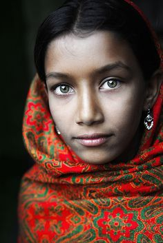 Taken by photographer David Lazar in Putia, Bangladesh, this portrait features a young lady's green eyes. She is wearing a traditional Bangladeshi textile around her head and shoulders.