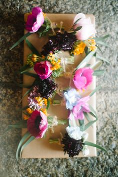 | SPRING TROPICAL WEDDING |  Natural, mis-matched buttoholes, made with bright flowers poppies, garden roses, anemones, fritillaria, scabious, delphiniums, lilac & eucalyptus for their beautiful wedding at Polhawn Fort on the coast of Cornwall.