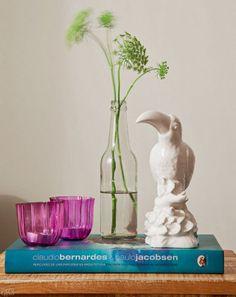 Receita de um arranjo delicado: o livro apoia dois porta-velas de vidro Votive (Etna, R$ 12,99 cada), garrafinha com ramos de flor de cenoura e tucano de porcelana (Oren, R$ 88).