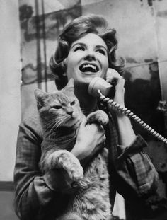 Yale Joel: Actress Julia Meade holding her cat at home in her apartment, New York, March 1960