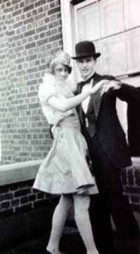 A black and white photo of a couple wearing formal dress of the 1920s as if preparing to go dancing. UM students