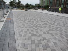 A row of permeable pavers (left) covers a drain pipe that will pick up water in the south facing plaza and redirect toward two drywells where it will be filtered back into the ground.