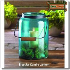 Blue Jar Candle Lantern - Fill your living space with azure glow! This country-style jar lantern is made from gorgeous blue glass and fitted with a metal handle with wooden grip at top. Great for indoor or outdoor spaces.