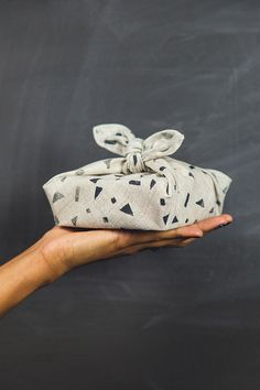 A lovely, cloth wrapped gift -especially liking the rough, natural fabric bedecked with blue shapes!