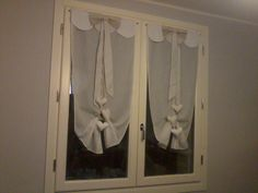 Tende a finestra con festoni e fiocco. Cuoricini sospesi con legaccio per arricciare le tende