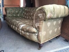 Early 20th century cosy three seater sofa in original cover.Nice turned mahogany legs standing on brass castors.