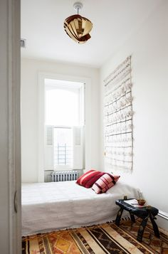 Gold light fixture in white, boho bedroom with tapestry on wall