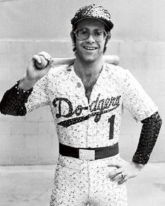 English singer and songwriter Elton John poses in Bob Mackie's now famous sequined white Dodgers uniform at Dodger Stadium in Los Angeles, October Elton John Glasses, Elton Jon, Elton John Lyrics, Lgbt, Dodger Stadium, Famous Singers, 70s Singers, Tiny Dancer, Music Icon
