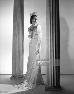 Barbara Cushing Mortimer (aka Barbara Cushing, <a gi-track='captionPersonalityLinkClicked' href=/galleries/search?phrase=Babe+Paley&family=editorial&specificpeople=968974 ng-click='$event.stopPropagation()'>Babe Paley</a>, Barbara Cushing Mortimer Paley, Mrs Stanley Grafton Mortimer, Mrs William Paley) She is standing in between two columns, wearing an embroidered gown and a feathered headpiece.