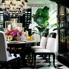 I've always been drawn to pin stripes, houndstooth, plaid, etc. Anything that mimics men's suits. And this dining room, to me, is simply handsome and tailored. A dash of femininity is added with the layered vases, pink blossoms, sexy lines on the chairs and the main spectacle...the lavish crystal chandelier. #Ralph Lauren