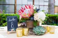 Bright wedding centerpieces -  king protea, succulents, and blue thistle with chalkboard table number {matthew foster photography}