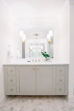 White and grey bathroom features a nook filled with a gray vanity adorned with gold knobs topped with white marble under a framed mirror illuminated by Vendome Single Sconces and a Schoolhouse Electric Luna Natural Brass Pendant alongside a white marble hex tiled floor.