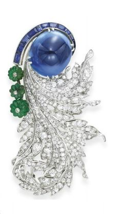 A DIAMOND, SAPPHIRE AND EMERALD BROOCH, BY PAUL FLATO  Set with a detachable sugarloaf sapphire, weighing approximately 49.51 carats, accented by a tapered coil of calibré-cut sapphires and a graduated line of three carved emerald beads, each topped by a collet-set diamond, extending old European and single-cut diamond curling leaves, mounted in platinum