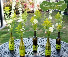 wine bottle centerpieces---another use for all those empty wine bottles! Wine Bottle Flowers, Wine Bottle Vases, Wine Bottle Centerpieces, Empty Wine Bottles, Wine Bottle Crafts, Diy Centerpieces, Bottle Decorations, Table Decorations, Glass Bottles