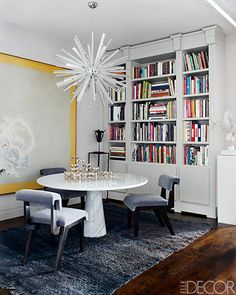 A vintage Venini light fixture hangs above a 1970s marble dining table by Angelo Mangiarotti; the custom-made chairs are from Flair, the painting is by Cleve Gray, and the rug is a vintage Beni Ourain.