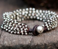 This bracelet made with 2.5mm silver plated bead woven together with dark brown wax cord and silver bell for closure