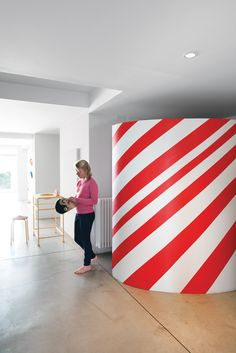 PLAYFUL FAMILY HOME IN BELGIUM Daughter Oona stands near the candy-striped wardrobe in the entryway.  Photo by Frederik Vercruysse.