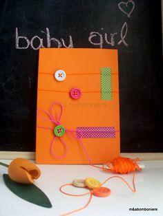 Μπομπονιέρα σε πορτοκαλί φακελάκι, με χρωματιστά κορδονάκια, πολύχρωμα κουμπάκια και πουά washi tape. Τιμή: 2,00 ευρώ.