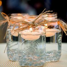 Table decor for backyard party   Mason jars with candles.  You could even color the water to match your color scheme.
